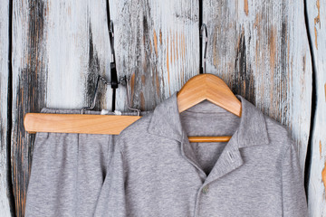 Gray pajama suit in wardrobe. Shirt and pants on hangers. Soft textile of sleepwear for comfort boy's sleeping.