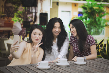 Three women taking photo in the cafe