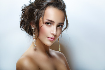 Beauty fashion portrait of young beautiful girl. Beautiful evening make-up, open shoulders, perfect skin and hair.