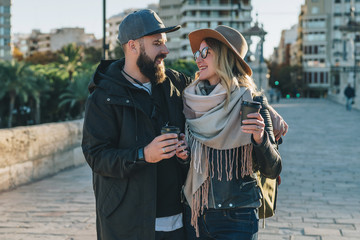 A couple of young tourists, friends are walking along the city street, drinking coffee while they are happily looking at each other. Vacation, travel, adventure, lifestyle. Blurred background.
