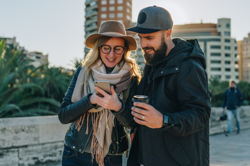 Couple of young travelers are standing on city street and using smartphone,holding cups of coffee.Girl shows guy an image on smartphone screen.Friends are walking around city.Lifestyle,social network.
