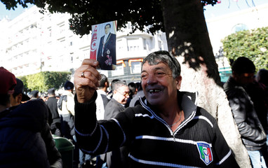 A man holds a picture of former Tunisian president Zine El-Abidine Ben Ali during demonstrations on the seventh anniversary of his ousting