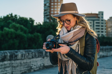 Backlight. Young smiling woman tourist, photographer, hipster girl dressed in hat and eyeglasses, stands on city street and uses camera, looks images on screen. Vacation, travel. Blurred background.