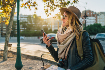Young woman tourist, hipster girl with backpack, camera,dressed in hat, glasses,sits on bench in city street,using smartphone and holding map.In background,in soft focus,road and cars.Vacation,travel.