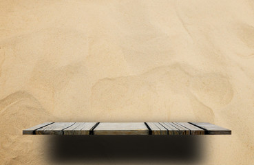 Empty wooden shelf counter on sandy background for product display