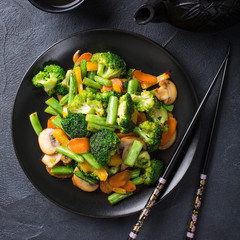 Hot stir fried vegetables on black plate. Healthy asian food concept with copy space.