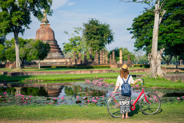 Young woman traveler travelling by bicycle into Wat Mahathat temple in the Sukhothai Historical...