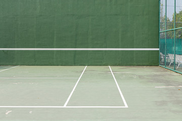Outdoor tennis court and green knock board with white lines for personal practice.