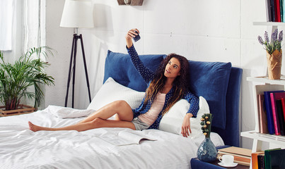 Attractive casual woman in  blue pajamas is messaging or taking selfie with smartphone in bedroom