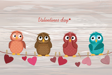 Cute colored owlet sitting on a rope. A red hearts