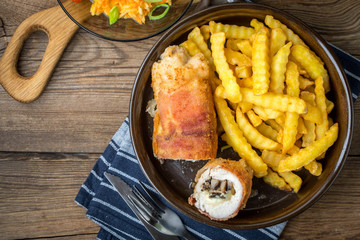 Fried chicken breast stuffed with mushrooms and cheese wrapped in ham served with fries and salad.