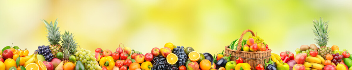 Fresh healthy fruits and vegetables in basket on natural blurry multicolored background.