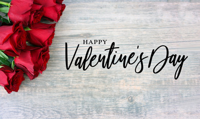 Happy Valentine's Day Text with Red Roses Over Rustic Wood Background