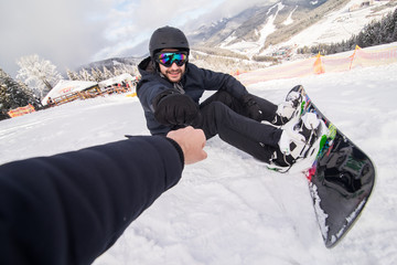Snowboarder fastens snowboard buckles sitting on the top of snow hill and give five