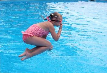 Girl jumping in open swimming pool