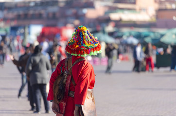 Water seller or water keeper Guerrab dressed in in typical colorful Moroccan costume at the market place in Marrakech