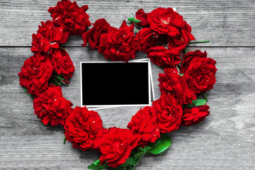 red rose flowers heart shaped with blank photo frame on rustic wooden background