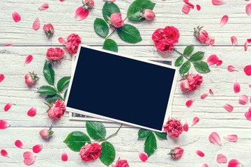 Flowers composition. frame made of pink rose flowers with blank photo frame