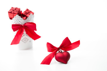 gifts in a white basket with a heart with a bow in red on a white background