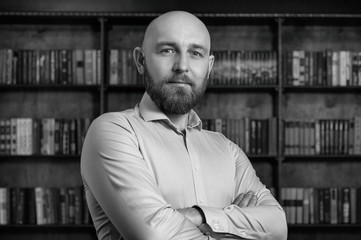 A bald man with a beard in the library.