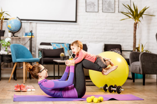 Young mother in sportswear doing exercise lifting with legs her baby son on the mat at home