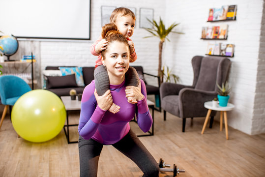 Young mother in sportswear doing exercise squating with her baby son at home