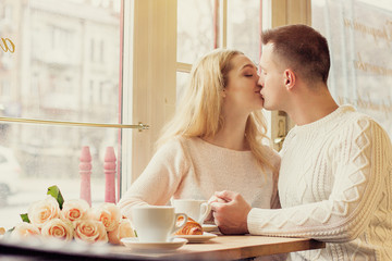 Young couple having romantic dinner in cozy french cafe. Man kissing his beautiful girlfriend while sitting in vintage restaurant. Celebration of their special date. Valentines day and love concept