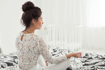 Fit young woman doing yoga and meditation pose on bed at home in the bedroom with white interior. Young woman meditating indoors, healthy lifestyle concept, back view