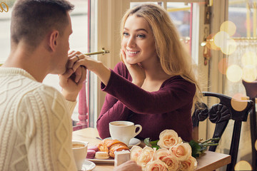 Back view man kissing his beloved woman hand while having romantic dinner in cozy french cafe. Happy young couple celebrating in vintage restaurant. Valentines day, love and togetherness concepts