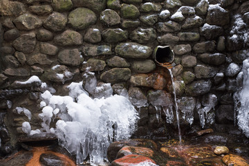 A stone source with ecologically clear water in the forest in winter. A stone source with ecologically clear water in the forest in winter. Wild stone water source or water spring