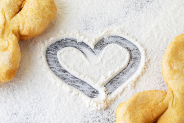 heart of flour on the table along with pastries from dough