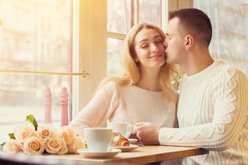 True love. Portrait of young couple have romantic lunch in cozy french restaurant. Man kissing his beloved girlfriend. Couple celebrating their special date. Valentines day and togetherness concept