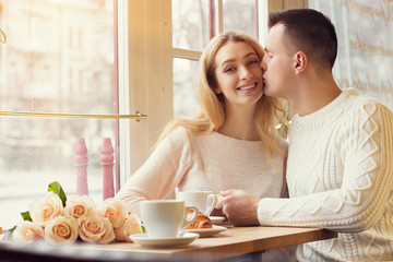 Portrait of handsome man kissing his smiling girlfriend while sitting in cozy french cafe. Young couple having romantic dinner in vintage restaurant. Celebration of Valentines day or birthday concept