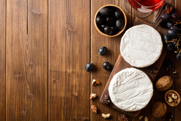 Camembert and brie cheese on wooden cutting board with grape and nuts.