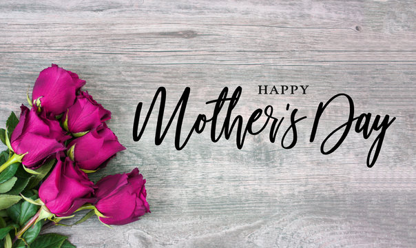 Happy Mother's Day Calligraphy with Pink Roses Over Rustic Wood Background