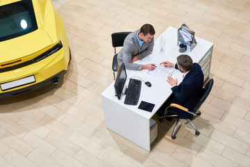 Above view of young handsome man reading purchase contract sitting at desk in dealership shop before buying luxury car, copy space