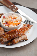 Grilled pork ribs in barbecue sauce and honey with sauerkraut on white plate. Snack to beer on a light stone table