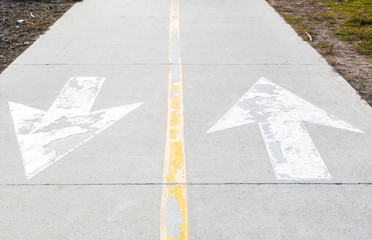 2 weathered white arrows pointing in opposite directions on a cement walkway