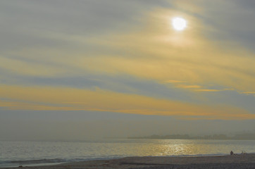 golden, smoky sky with sun shimmering on the water and a solitary person on the beach in Santa Barbara, California