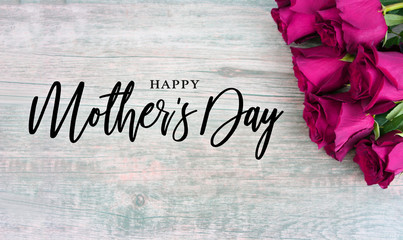 Happy Mother's Day Typography with Colorful Pink Roses in Corner Over Rustic Wood Background
