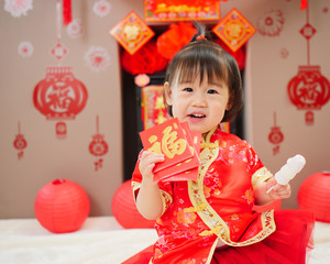 """Chinese baby girl  traditional dressing up with a """"FU"""" means """"lucky"""" red envelope"""