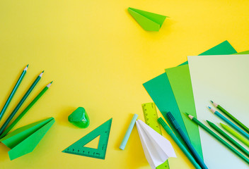 Creative, fashionable, minimalistic, school or office workspace with green supplies on yellow background. Flat lay.