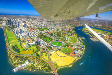 Aerial view of Perth Skyline in Australia. Scenic flight with wing of plane over Langley Park, New Perth Stadium, Cricket Pitch, WACA Ground and Swan River in Western Australia.