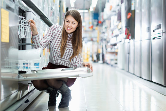 Modern female housewife buying dishwasher in domestic appliances section