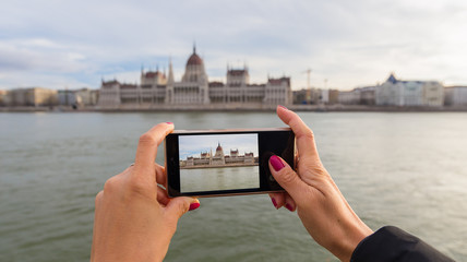 Smartphone held by woman hands. Photo of Budapest parliament building on the smartphone screen, taken from riverbanks of Danube river in BudaPest, Hungary
