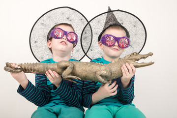 Happy children in elegant green clothes play at home with a stuffed crocodile. Boys in carnival glasses and a hat are posing for a fashion magazine