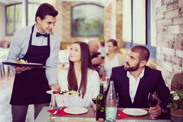 Waiter male bringing food for guests