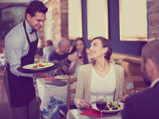 Waiter  male bringing food for man and woman guests
