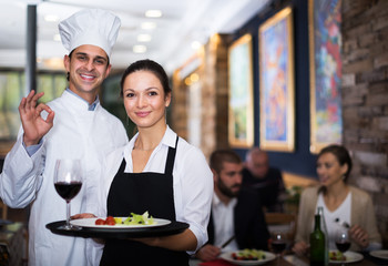 Waitress with chef in restaurant