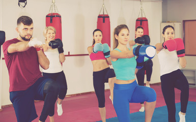 group women and their trainer are boxing in gym